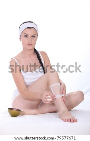 Attractive brunette waxing leg - stock photo