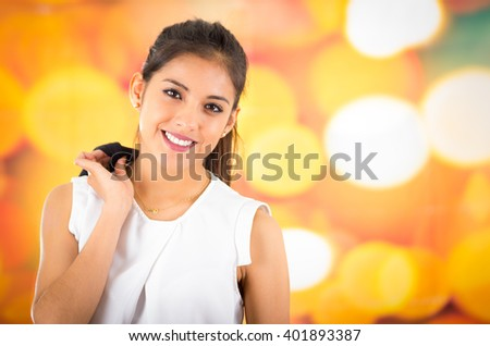 Attractive brunette wearing white shirt posing naturally and smiling beautiful to camera with blurry colorful background - stock photo