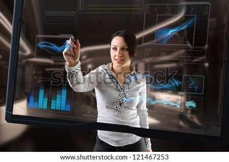 Attractive brunette with interface in futuristic interior. - stock photo