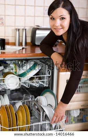 attractive brunette woman cleaning kitchen - stock photo