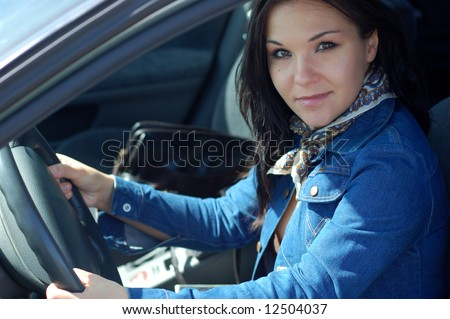 attractive brunette woman happy in new car - stock photo