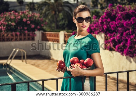 Attractive brunette woman holding a bowl of apples. Healthy food concept with copyspace. Girl looking away from camera.  - stock photo