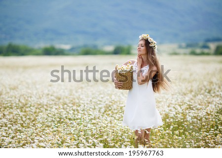 Attractive brunette woman in chamomile field. Young woman in wreath surrounded by chamomiles. Daisy flowers field. Summer portrait. - stock photo
