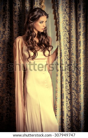 Attractive brunette woman in gorgeous evening dress posing by the vintage hangings. Beauty, fashion. - stock photo