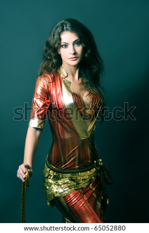 Attractive brunette woman in oriental fashion. Beautiful cabaret woman in bright oriental dancer dress. - stock photo