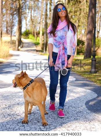 Attractive brunette woman in sunglasses on a walk with her brown dog. - stock photo