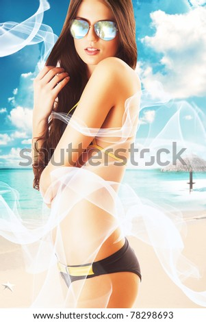 attractive brunette woman in white fabric on the beach - stock photo