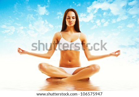 attractive brunette woman in yoga poseattractive brunette woman in yoga pose and sky - stock photo