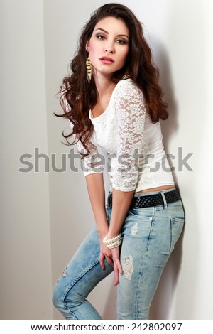 Attractive brunette woman posing by the wall.  - stock photo