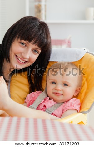 Attractive brunette woman posing with her baby while sitting in the kitchen - stock photo