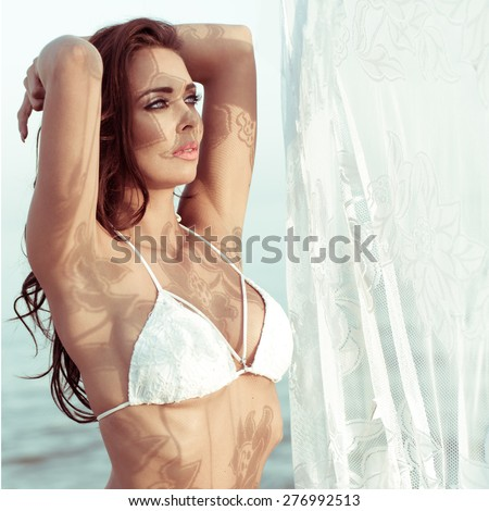 Attractive Brunette Woman Wearing White Bikini Standing with Hands Behind Head Near Lace Curtain Beside Water - stock photo