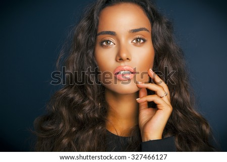 Attractive brunette woman with beauty long curly hair and colorful makeup. Fashion model with wavy hairstyle. Toned in warm colors. Studio shot, horizontal  - stock photo