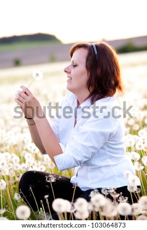 Attractive brunette woman with dandelion in meadow - stock photo
