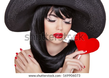 Attractive brunette woman with holiday makeup holding red heart isolated on white background - stock photo