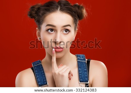 Attractive brunette woman, with top knot hairdo, wearing on denim jumpsuit, is holding finger near her mouth and thinking on the red background, in studio, waist up - stock photo