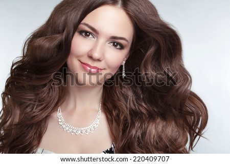 Attractive brunette young  smiling woman Model Portrait. Long healthy Wavy hair. Professional makeup. Jewelry  - stock photo