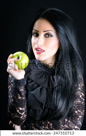 Attractive, brunette young woman holding a green apple against a black background - stock photo