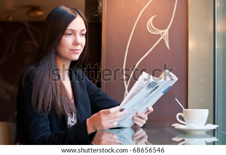 Attractive brunette young woman reads a magazine sitting in a cafe, shallow DOF, focus on face - stock photo