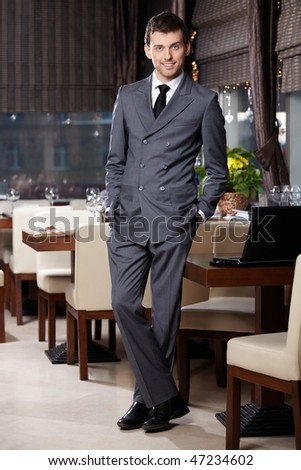 Attractive business man in suit stay in restaurant - stock photo
