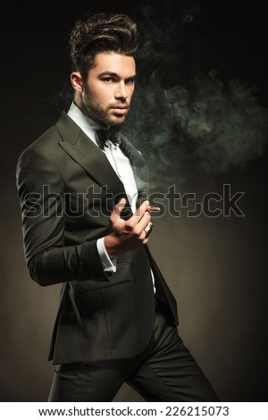 Attractive business man looking at the camera while holding a cigarette in his hand, walking forward. - stock photo