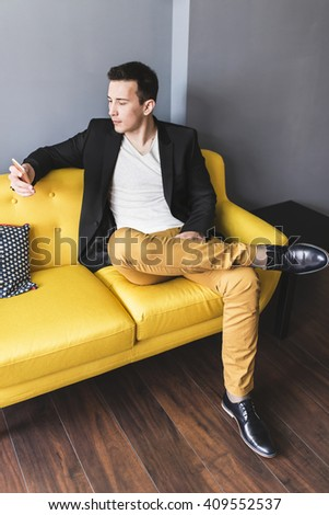 Attractive business man, sitting on a sofa in his office. Depth of field, focus on man's leg - stock photo