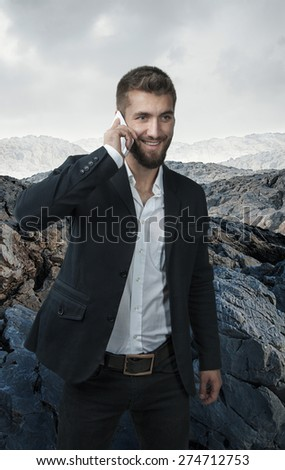 Attractive business man with a mobile phone alone in the mountains - stock photo