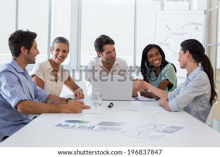 Attractive business people discussing at a business meeting in the office - stock photo