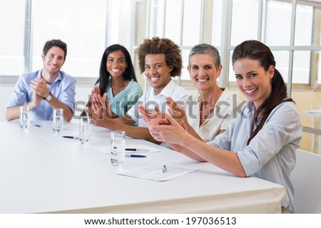 Attractive business people smiling at camera and clapping during a business meeting - stock photo
