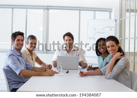 Attractive business people smiling at the camera during a business meeting - stock photo
