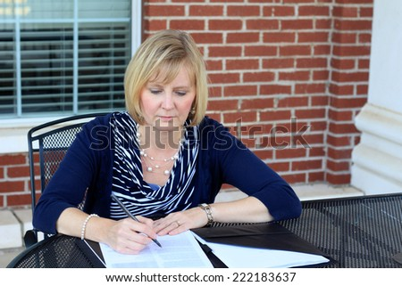 Attractive Business Professional Business Woman Working on Paperwork Wearing a Blue Shirt  - stock photo