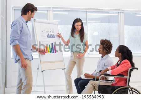 Attractive business team presenting graphs and their work to fellow employees - stock photo