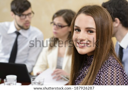 Attractive business woman at the office leading a group - stock photo