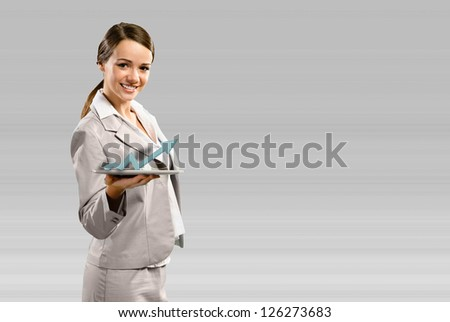 attractive business woman holding a tablet with a sign of the growing graph, financial concept - stock photo