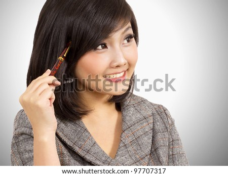 attractive business woman holding pen against her head - stock photo