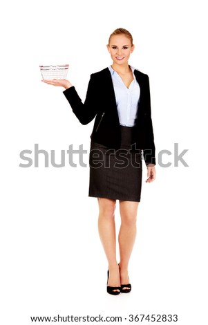 Attractive business woman holding small shopping basket - stock photo