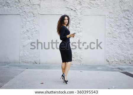 Attractive business woman in black dress with long curly hair posing against a white brick wall with copy space area for your text o design and writing a text message on her  digital smartphone - stock photo