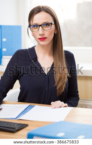 Attractive business woman in glasses at her workplace in office. Beautiful caucasian girl in dark shirt with long hair working at the desk - stock photo