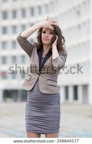 Attractive business woman in town. Urban young woman talking by phone adjusting her hairstyle - stock photo