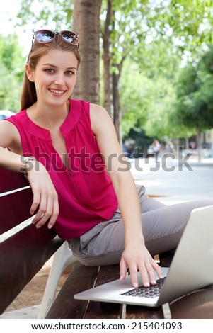 Attractive business woman sitting and working on her laptop computer while relaxing on a wooden bench in a city street with green trees during a sunny day, outdoors. - stock photo
