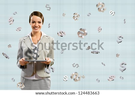 attractive business woman smiling and holding a tablet, with a dollar sign, concept of business success - stock photo