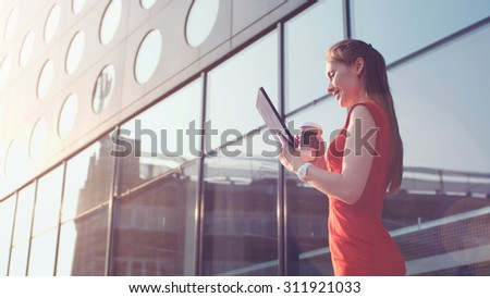 Attractive business woman using digital tablet walking in the city. Sexy woman wearing red dress enjoying morning, drinking coffee, reading news. Lens Flare. - stock photo