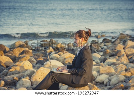 attractive business woman working on computer sitting on some rocks at the beach looking up to sky thinking about freedom - stock photo