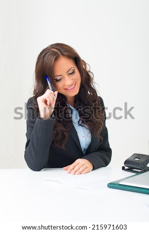Attractive business woman working with documents in office. - stock photo
