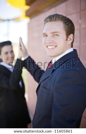 Attractive businessman and businesswoman giving high-five - stock photo