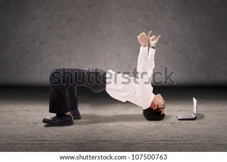 Attractive businessman break dancing with thumbs-up and laptop computer. shot in studio - stock photo