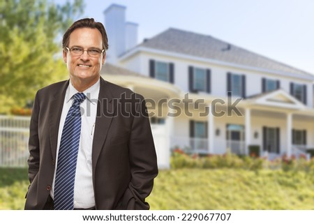 Attractive Businessman In Front of Beautiful New Residential Home. - stock photo