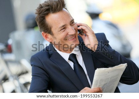Attractive businessman in town talking on mobile phone - stock photo