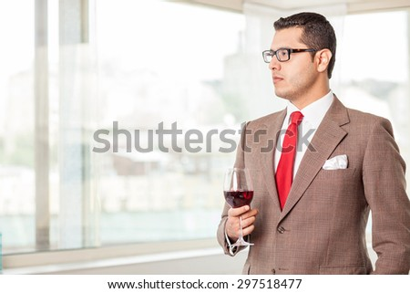Attractive businessman is hearing his colleague with attention. He is looking aside seriously. He is holding a wineglass with red wine. Copy space in left side - stock photo