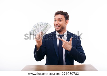 Attractive businessman is holding money and pointing his finger at it boastfully. He is smiling and sitting at the table. Isolated on white background and there is copy space in the left side - stock photo