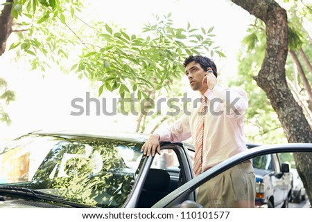 Attractive businessman leaning on a car's top while making a phone call in a leafy street. - stock photo